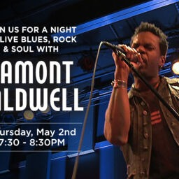Lamont Caldwell singing on blue light stage.